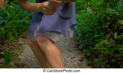 Young woman in tropical forest applies mosquito spray on...