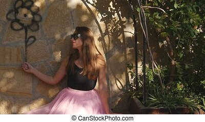 Young woman in tulle skirt sitting near the wall