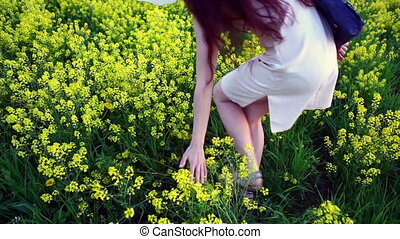Young Woman in Vintage Dress is walking through Yellow Field touching the hand of flowers