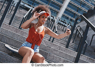 Young woman in visor and earphones free style on the street sitt