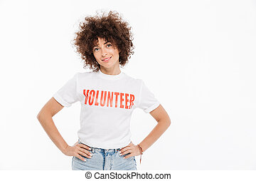 Young woman in volunteer shirt standing with hands on hips...