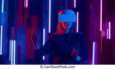 Young woman in VR headset looks around and wonders how amazing. Virtual reality helmet