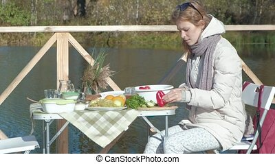 young woman in warm clothes, a picnic by the river on a wooden bridge, cutting vegetables, weekends, cold weather, outdoor recreation, tourism