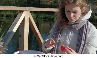 young woman in warm clothes, a picnic by the river on a wooden bridge, cutting vegetables, weekends, cold weather, outdoor recreation, tourism,close up