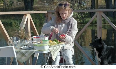 young woman in warm clothes, a picnic on the river bank on a wooden bridge, cutting vegetables, a dog playing nearby, weekends, cold weather, camping, tourism