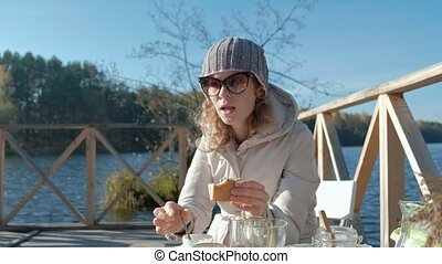 young woman in warm clothes, eating a burger, a dog is playing nearby, a picnic by the river on a wooden bridge, weekend, cold weather, camping, tourism