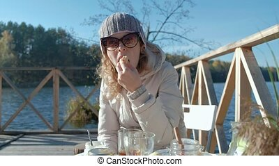 young woman in warm clothes, eating a burger, a picnic by the river on a wooden bridge, weekend, cold weather, camping, tourism