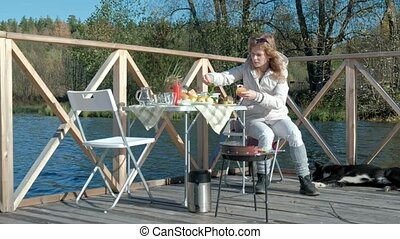 young woman in warm clothes, preparing vegetables and meat on the grill, preparing a burger, a dog playing nearby, a picnic on the river bank on a wooden bridge, a weekend, cold weather, outdoor recreation, tourism