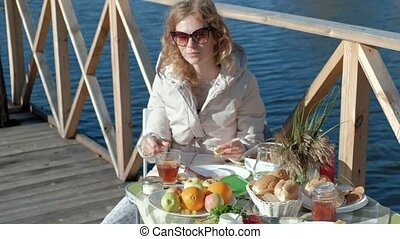young woman in warm clothes, sitting at the table, drinking tea, eating pancakes with jam, picnic by the river on a wooden bridge, weekend, cold weather, camping, tourism