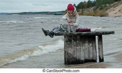 young woman in warm clothes sitting by the ocean, on a wooden coil, drinking hot tea from a thermos, cold weather, storm