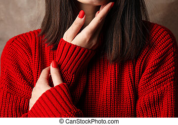 Young woman in warm red sweater on brown background. Space for text