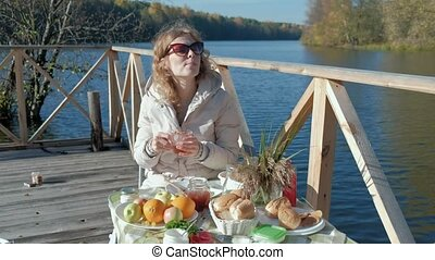 young woman in warm sunglasses, sitting at the table, drinking tea, eating pancakes with jam, picnic by the river on a wooden bridge, weekend, cold weather, camping, tourism