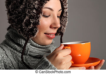 Young woman in warm winter hat drinking hot tea
