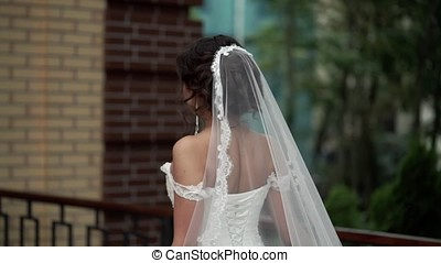 Young woman in wedding dress walks on terrace
