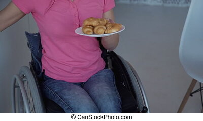 Young woman in wheelchair holding plate with croissans in...