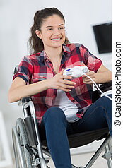 young woman in wheelchair playing video games