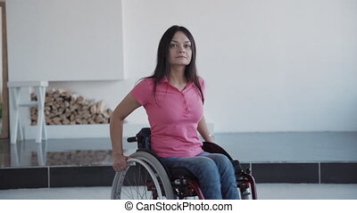 Young woman in wheelchair spending weekend time at home -...