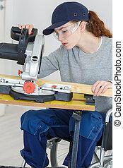 Young woman in wheelchair using circular saw