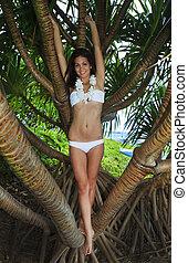 young woman in white bikini and flower lei