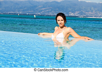 Young woman in white bikini resting on holidays