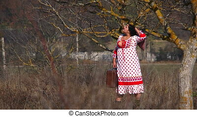 Young Woman In White Dotted Dress Walking At Meadow