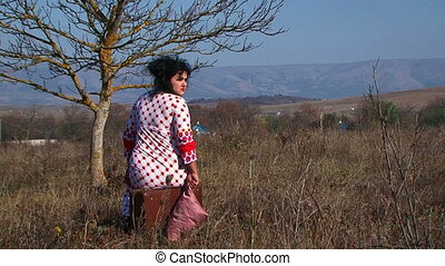 Young Woman In White Dotted Dress Sitting On Suitcase At Nature