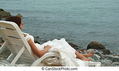 Young Woman In White Dress Lying On Chaise-Longue