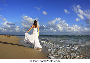 Young woman in white dress on a beach