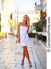 Young woman in white dress on street of summer tourist city