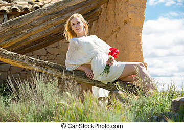 Young woman in white dress sitting on tree and holding poppies plants