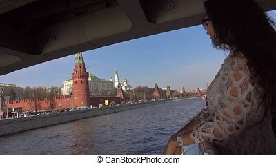 Young woman in white dress standing on the deck of boat passing Moscow Kremlin. Travel to Russia concept. 4K shot