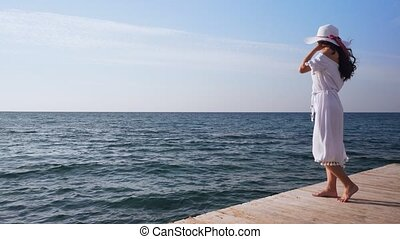 Young woman in white dress stands on wooden pier