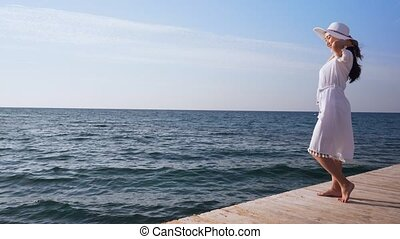 Young woman in white dress stands on wooden pier.