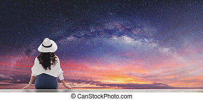 Young woman in white hat and cloth looking at beautiful starry sky with milky way at dawn