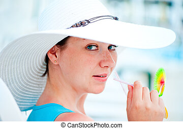 young woman in white hat drinking a cocktail