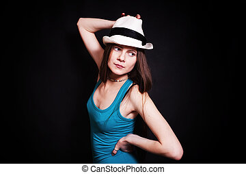 young woman in white hat on black background