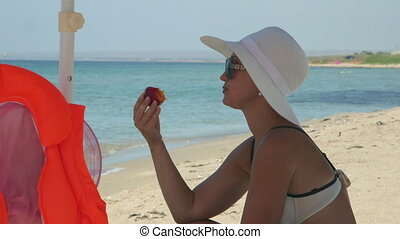 Young woman in white hat on summer vacation eating peach at sandy beach