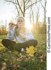 Young woman in white hoodie blowing soap bubbles in the autumn park