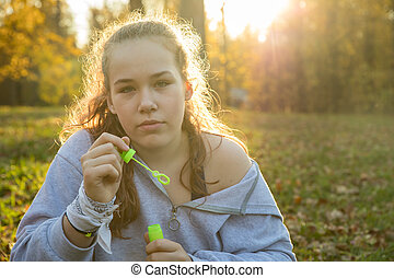 Young woman in white hoodie holding soap bubbles in the autumn park