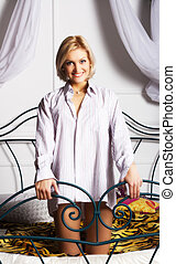 young woman in white shirt posing on the bed