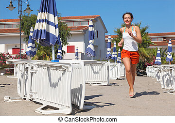 young woman in white shirt running on beach near lounges and umbrellas, palms and houses