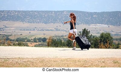 young woman in white shorts happily running with suitcase