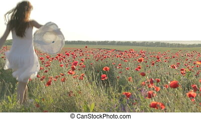 CLIP EDIT Young woman in white sundress waking through red poppies field, holding white hat, twisting, dancing enjoying free time, resting on nature, smiling, flirting, touching petals of flowers.