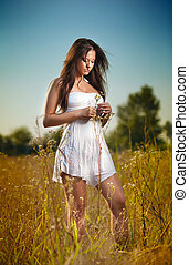 Beautiful young woman in wild flowers field on blue sky background. Portrait of attractive brunette girl with long hair relaxing in nature, outdoor shot. Lady in white short dress enjoying nature
