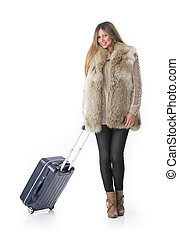Young woman in winter clothes with a rolling suitcase.