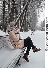 Young woman in winter park sitting at bench, smiling
