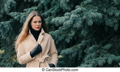 Young woman in winter park with pine slow motion