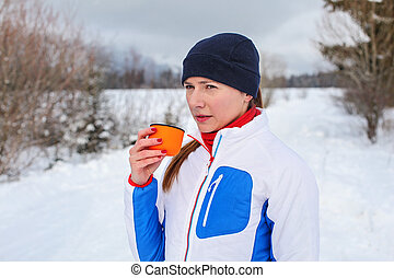 Young woman in winter sport jacket drinking hot tea from orange thermos flask cup on cold cloudy day with snow covered landscape in background.