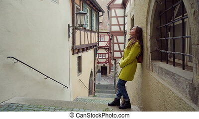 Young woman in yellow coat girl stands at the wall of the house in small Germany city. Happy girl enjoying walking in cute small half-timbered town with old houses in Schwabisch Hall, Germany