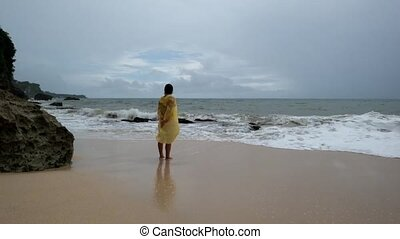 Young woman in yellow rain coat on the beach in heavy rain...